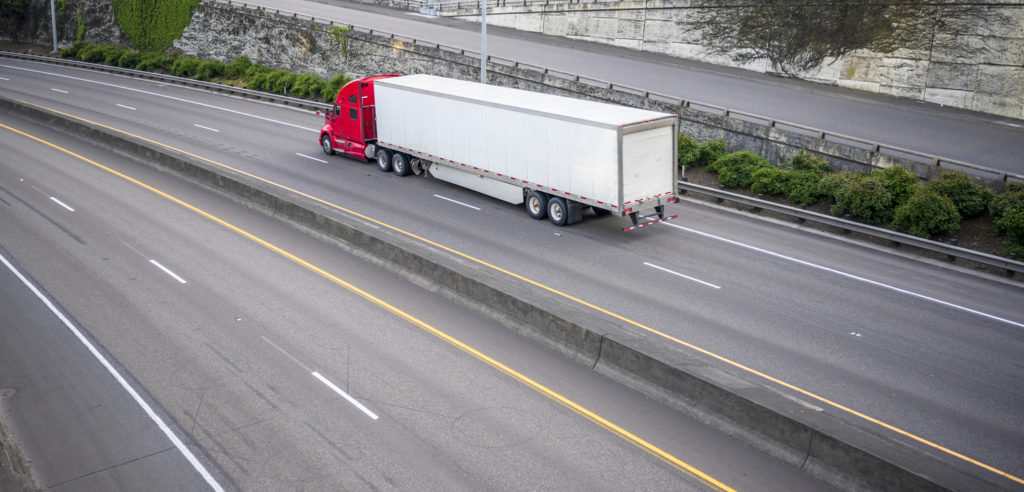 Red big rig long haul semi truck with dry van semi trailer running on divided wide highway