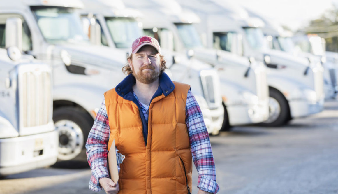Man standing in front of semi-truck fleet